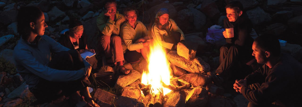 Group enjoys campfire on multi-day Tuolumne rafting trip.